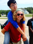 A counselor gives a piggy-back ride to a camper.